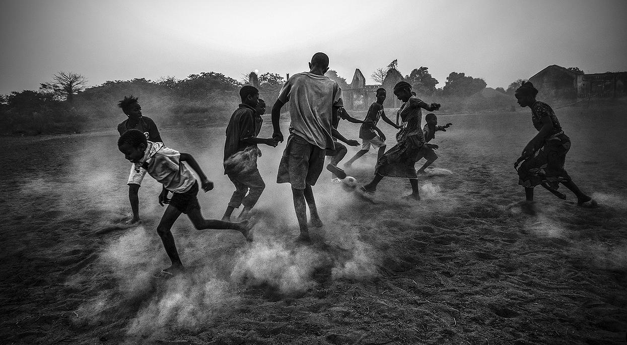 Youth Group playing ball in a field, now soccer field, that was formerly a military barracks of the former Portuguese colonies in the village of Dulombi, Galomaro, Guinea © Daniel Rodrigues