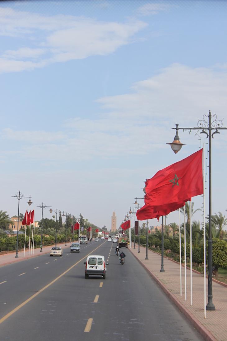 Avenida com bandeira de Marrocos e Koutoubia ao longe ©Viaje Comigo